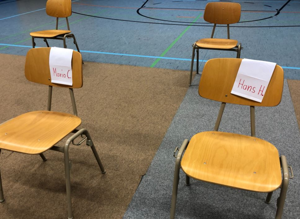 """Bild von zwei Stühlen mit aufgelegten Namenszetteln als """"Platzreservierung"""""""